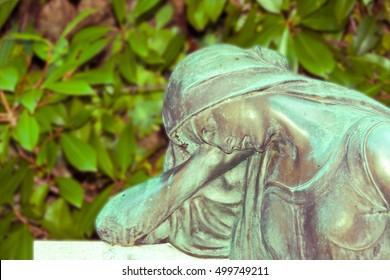 Statue of a sad woman , De focused background , vintage saturation