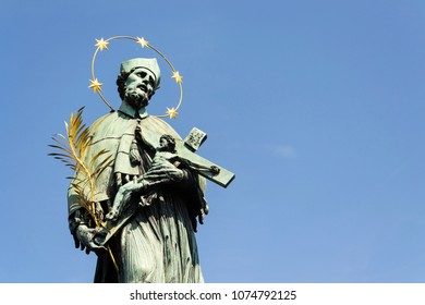 Statue of Saint John of Nepomuk holding crucifix with Jesus Christ on Charles Bridge in Prague, Czech Republic, sunny day, clear sky