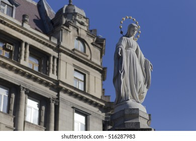 A statue of saint Mary with old building and blue sky background