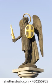 Statue of Saint Michael the Archangel with golden sword and shield near Holy Transfiguration Cathedral in Donetsk, Ukraine - 2016, September 11. Close up. Clear blue sky in the background.