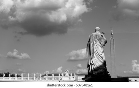 Statue of Saint Peter in St. Peter's Square in Vatican City, Rome. A pigeon is going to land on the shoulder. Black & White adjustment.