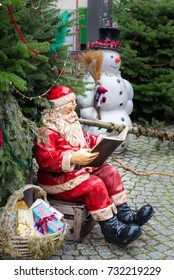 Statue of a Santa Clause sitting on a box reading a book with a snowman in the background and evergreen trees all around