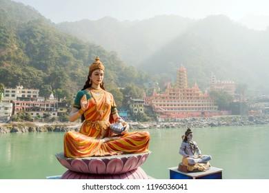 Statue of sitting goddess Parvati and Statue Shiva on the riverbank of Ganga in Rishikesh
