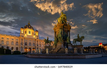 Statue in a square between museums during dawn with dramatic sky and lights
