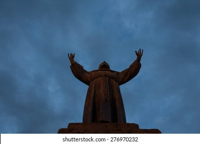 The Statue of St Francis of Assisi viewed from below under a nigh sky.