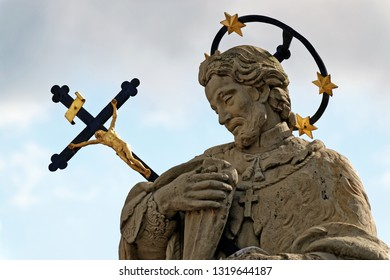 Statue of St. John of Nepomuk on Wollestraat Bridge, Bruges, Belgium with a halo of five stars, commemorating the stars that hovered over the Vltava River and a large crucifix.