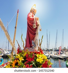The statue of St. Peter the patron saint of seafarers against the background of the fishing port with flowers at the foot side view