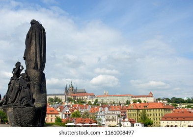 A statue stands guard on the Charles Bridge, Prague. Behind is a view over the city towards Prague Castle. The sky is blue with looming storm clouds.