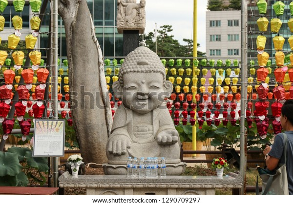 Statue of stone Buddha in the territory of the Buddhist temple Jogyesa, the center of Zen Buddhism in Korea. Seoul, South Korea. August 14, 2018