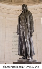A statue of Thomas Jefferson standing in the Thomas Jefferson memorial near the capitol mall in Washington DC.