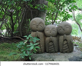 Statue of three bald men (known as Jizo) in a Japanese garden