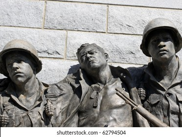 Statue of two soldiers helping an injured soldier emphasis on faces.