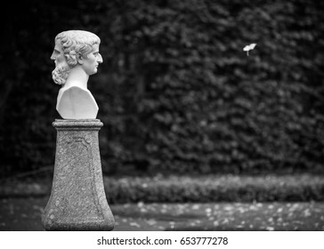 A statue of two-faced Janus, Greek god of time. Black and white photo
