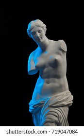 Statue of Venus in blue light on a black background