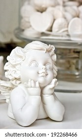 Statue of a white child angel, with heart candies in the back ground. Love concept. Useful for celebrations like wedding, anniversary, baptism. Clipping path of the angel included