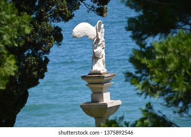 The statue of the winged goddess Nike on the pedestal against the sea