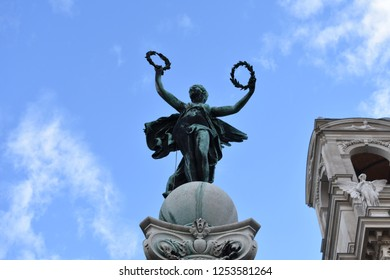 Statue of winged woman holding laurel wreath in front of Art museum in Vienna. The Greek goddess Nike / The Winged Victory of Samothrace