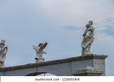 Statue of a woman and an eagle at the entrance to a garden on the background of the cloudy sky.