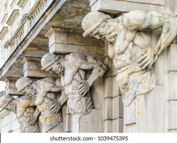Statues of the Atlases holding a portico. Stone sculptures of male torsos