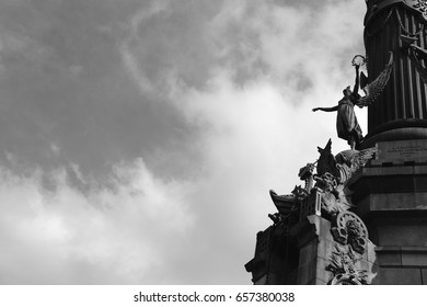 Statues from Barcelona Columbus monument against sky, black and white