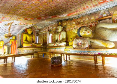 Statues of Buddha sitting and reclining in the ancient Buddhist cave temple at Dambulla, Sri Lanka.