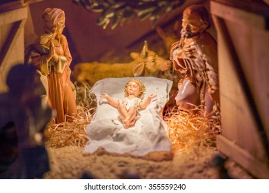 Statues in a Christmas Nativity scene, the Blessed Virgin Mary and Saint Joseph watch over the Holy Child Jesus in a manger in the straw while the ox and the donkey are warming air