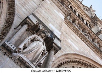 statues at the facade of notre dame, in paris