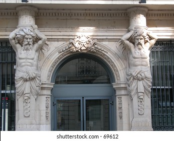 Statues of two strong men seeming to hold the entire building.