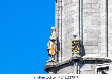Statues of watchman in body armour holding trumpet  and crossed shield, and lion with heraldic shield on  Saint Bavo  Cathedral tower in Ghent, Belgium