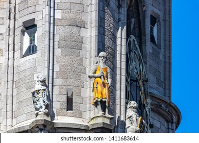 Statues of watchman in yellow body armour holding axe and lions on  Saint Bavo  Cathedral tower in Ghent, Belgium