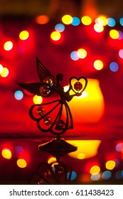 statuette of an angel on a red background with a colored bokeh in romantic atmosphere