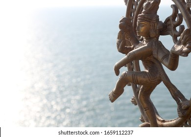 Statuette of a dancing bronze Shiva against the background of the sea. Room for text.