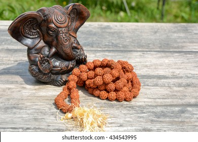 Statuette of Hindu God Ganesha and a rosary from the fruit of the Rudraksha tree
