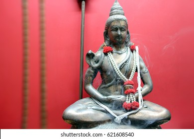 A statuette of a meditating shiva on a red background. Lord Siva is sitting in a lotus position with a snake around his neck.