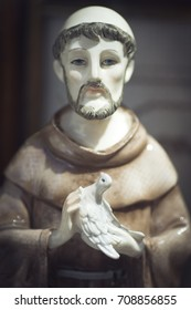 Statuette of St. Francis of Assisi with a white dove in his hands. Selective focus