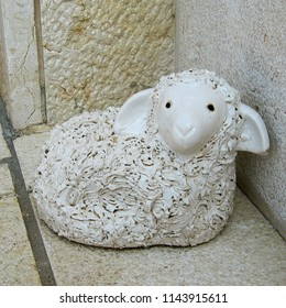 Statuette of white stone in the shape of a small lamb on the wall background