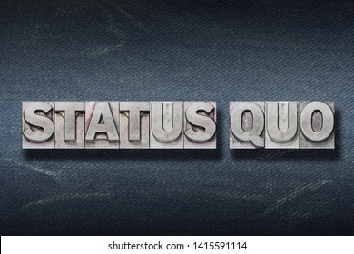 status quo - ancient Latin saying meaning «current condition» made from metallic letterpress on dark jeans background