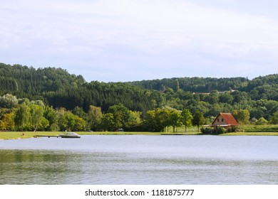 Stausee Lake. Wooden cabin and motor boat at the pear. Lake in Burgenland. Austria. Holidays by the lake.