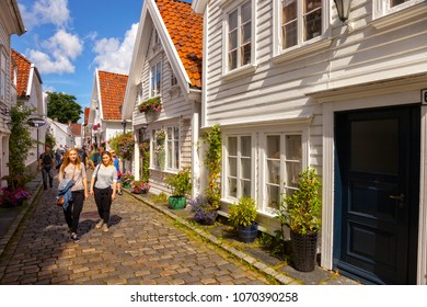 STAVANGER, NORWAY - AUGUST 01, 2017: Tourists walking a short street with small old wooden home. Stavanger is one of most famous cruise travel destinations in Europe.