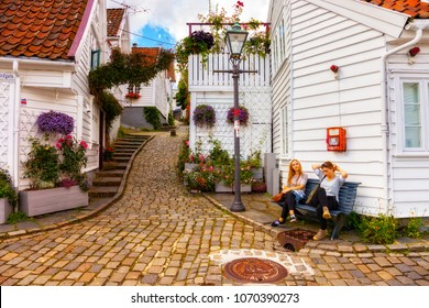 STAVANGER, NORWAY - AUGUST 01, 2017: Two girls sit on a bench in front of a small old wooden home.. Stavanger is one of most famous cruise travel destinations in Europe.