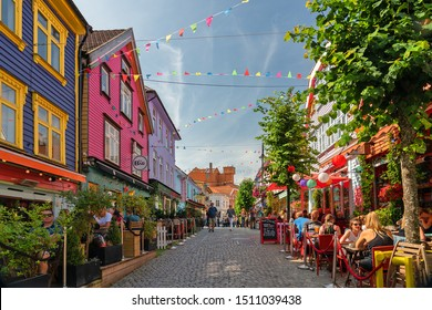 Stavanger, Norway - August 19, 2019: Tourists on historical street in Stavanger old town with multicolor wooden houses.