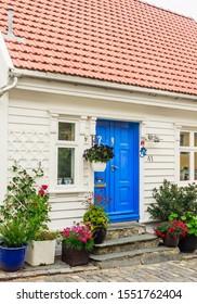 STAVANGER, NORWAY - JULE 18, 2019: Pretty Norwegian cottage with flowers on Ovre Strandgate in the old part of Stavanger known as Gamle Stavanger