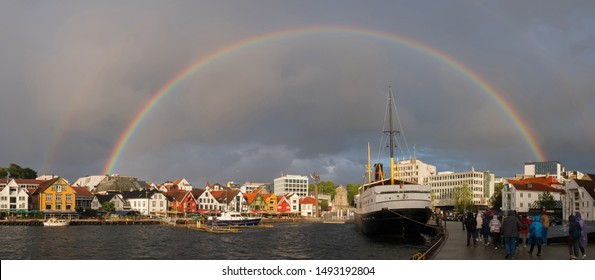 Stavanger, Norway - July 2019: The harbour in Stavanger city. This area is called Vågen. Evening with the rainbow