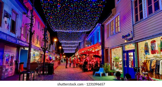 Stavanger, Norway -  November 15, 2018   Øvre Holmegate- The colourful street in Stavanger decorated with christmas lights and people having a drink on the pubs