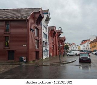 STAVANGER, NORWAY, SEPTEMBER 9, 2019 : street with Traditional red and white wooden houses in Gamle Stavanger. Gamle Stavanger is a historic area of the city center of Stavanger. Rainy moody day