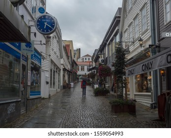 STAVANGER, NORWAY, SEPTEMBER 9, 2019 : street with Traditional white wooden houses in Gamle Stavanger. Gamle Stavanger is a historic area of the city center of Stavanger. Rainy moody day. Travel and