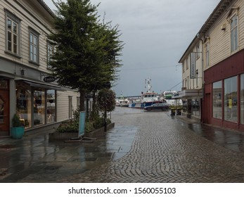 STAVANGER, NORWAY, SEPTEMBER 9, 2019 : street with Traditional white wooden houses in Gamle Stavanger and view on port and ships. Historic area of the city center of Stavanger. Rainy moody day. Travel