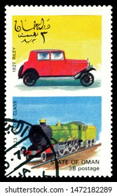 STAVROPOL, RUSSIA - July 31. 2019: A stamp printed in State of Oman shows antique locomotive Castle Class 1923 and car Riley 1927, series, circa 1972