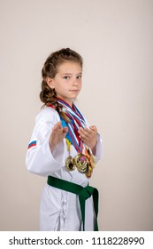 Stavropol, Russia - May 20, 2018: girl in a kimono with medals in a photo studio. An athlete achieving success in taekwondo.