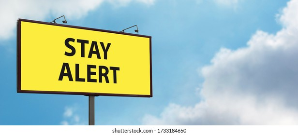 Stay Alert yellow warning sign on blue sky background. Large billboard with the slogan text. Staying alert after easing coronavirus lockdown restrictions, end of Covid-19 quarantine concept